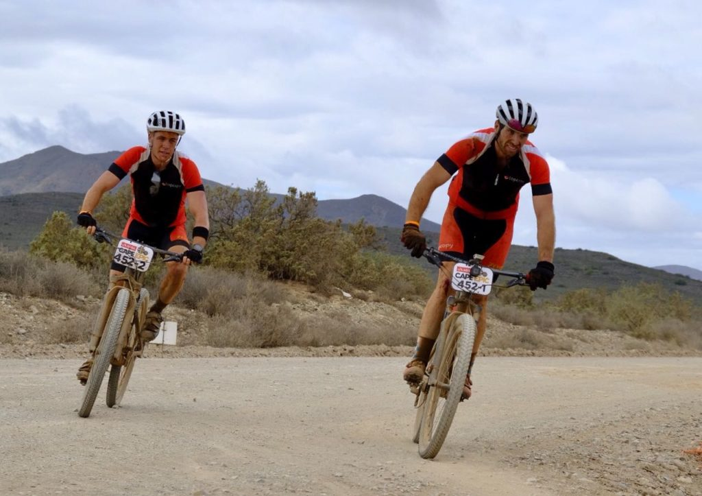 two men in red on mountain bikes